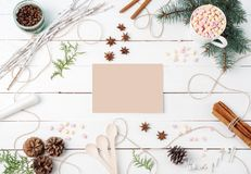 Frame composition of cocoa with marshmallow, cinnamon, anise stars, coffee seeds, fir tree, spoons and ingredients with clear card Stock Photo