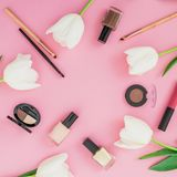 Frame composition with tulips flowers and cosmetics on pink background. Top view. Flat lay home feminine desk. Frame composition with tulips flowers and stock photos