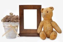 Frame de madeira, urso da peluche e potenciômetro de flor Imagem de Stock