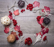 Frame decorative balls made of rattan, autumn leaves, plants, berries Viburnum on wooden rustic background top view close up space Stock Photography