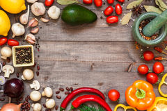 Frame of different fresh organic vegetables and spices on wooden table. Healthy natural food background with copy space. Top view royalty free stock photos