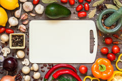 Frame of different fresh organic vegetables and spices on wooden table. Healthy natural food background with copy space. Stock Photos