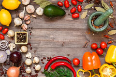 Frame of different fresh organic vegetables and spices on wooden table. Healthy natural food background with copy space. Top view Stock Images