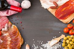 Frame of different Spanish appetizer, like fuet, jamon, chorizo, bacon and lomo embuchado with red wine and olives. Frame of different Spanish appetizer, like Royalty Free Stock Photography
