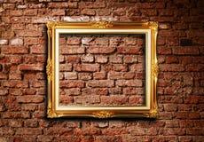 Frame dourado na parede de tijolo do grunge Imagem de Stock