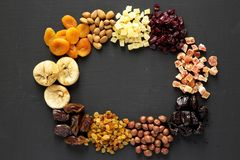 Frame of dried fruits and nuts on a black background, top view. Overhead, from above, flat lay royalty free stock photography