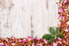 Frame of dried wild rose petals and tea grains on old board, copy space for text Royalty Free Stock Photo