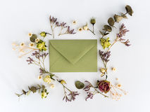 Frame of dry flowers and envelop on white background. Flat lay, top view Royalty Free Stock Photos