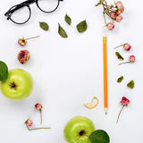 Frame of dry rose leaves, green apple, pencil and glasses Royalty Free Stock Image