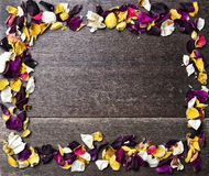 Frame with dry rose petals on wooden background Stock Photography
