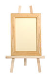 Frame on easel. Easel with wooden frame on white stock photography