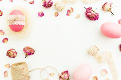 Frame of Easter pink eggs with twine, flowers and tapes on white background, Top view, Fat lay. Easter holiday Stock Photography