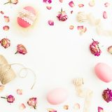 Frame of Easter pink eggs with twine, roses flowers and tapes on white background, Top view, Fat lay. Easter holiday Stock Photos