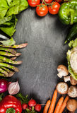 Frame of farm fresh vegetables on slate. Frame or border of assorted farm fresh vegetables on slate with copyspace including carrots, asparagus, tomato, pepper royalty free stock image