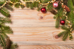 Frame of fir branches with Christmas decorations on a light wooden background Royalty Free Stock Photo