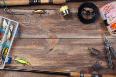 Frame fishing tackles and fishing baits in boxes on wooden board background stock photography