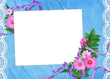 Frame with flowers on the blue background. White frame with flowers, plants and ribbon on the blue background Royalty Free Stock Photography