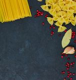 Frame for food. Pasta ingredients. Cherry tomatoes, spaghetti pasta, garlic and spices on a dark grunge background, copy space, stock image