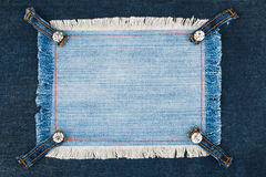 Frame with four straps jeans and rhinestones, lies on the dark denim Stock Photography