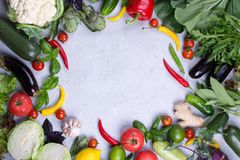 Frame of fresh organic vegetables on a gray concrete background . Healthy natural food top view, copy space . Bok choy pepper cabbage greens artichoke zucchini royalty free stock photos