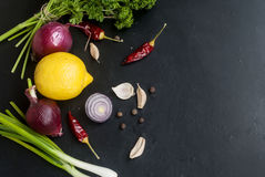 Frame with fresh organic vegetables and herbs. Lemon, red onion, green onions, herbs, parsley, chilli, pepper spices pepper on a black background. Overhead view Stock Image