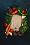 Frame with fresh organic vegetables and herbs. Red onion, green onions, herbs, parsley, chilli, pepper spices pepper on a black background. Overhead view . Frame Stock Photos