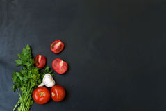 Frame with fresh organic vegetables and herbs. Red onion, green onions, herbs, parsley, chilli, pepper spices pepper on a black background. Overhead view . Frame Stock Image