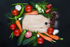 Frame with fresh organic vegetables and herbs. Red onion, green onions, herbs, parsley, chilli, pepper spices pepper on a black background. Overhead view . Frame Royalty Free Stock Photography