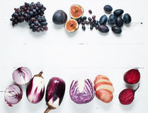 Frame of fresh purple fruit and vegetables on wooden background Royalty Free Stock Images