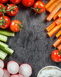 Frame of fresh vegetable crudites. Frame of healthy vegetarian fresh vegetable crudites with sliced carrot and cucumber batons, radish, cherry tomatoes and a Stock Photos