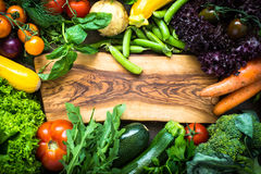 Frame of fresh vegetables around cutting board. Healthy food background. Organic farmer vegetables. Top view Stock Photos
