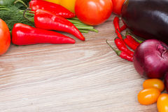 Frame of  fresh vegetables. Blank wooden table  with border of  fresh colorful vegetables Stock Images