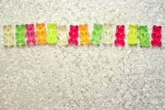 Gummy bears frame. Frame from fruit gummy bears candies, top view on a grey background with copy space Stock Image