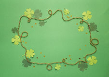 Frame of golden beads and clover leaves on a green background. S Stock Images