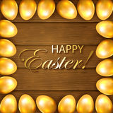 Frame from golden Easter eggs on wooden background Royalty Free Stock Photos