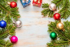 Frame from green branches of a Christmas tree with different multicolor toys and on a blue board with a place for the inscription. Frame from green spruce stock photography