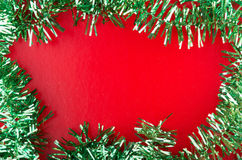 Frame of green Christmas tinsel on red background Stock Photo