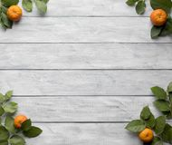 Frame of green leaves and mandarins on wooden vintage boards. stock images