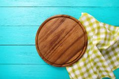 Food concept. Pizza Cutting board and green plaid tablecloth on blue wooden background. Top view and copy space. Mock up. Frame of green plaid texture on blue Royalty Free Stock Photography