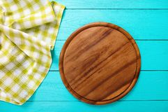 Food concept. Pizza Cutting board and green plaid tablecloth on blue wooden background. Top view and copy space. Mock up. Frame of green plaid texture on blue Royalty Free Stock Photos