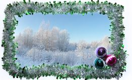 Frame of green and silver Christmas tinsel with four colored glass balls. Winter landscape inside. Snow and white trees.n royalty free stock images