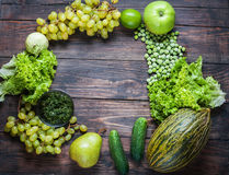Frame of green vegetables and fruits on dark wooden background. Top view. Royalty Free Stock Photo