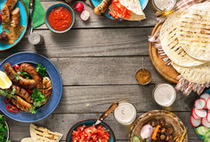 Frame of grilled sausage, lager beer, tortilla and different dis. Frame of grilled sausage, tortilla wraps, lager beer and different dishes on wooden table, top Stock Images