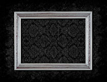 Frame on Grungy wallpaper. Grungy silver frame on black floral wallpaper Royalty Free Stock Photography