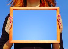 Frame in hands. The photo of wood picture frame in hands of a woman with pink nails. You can use another fill inside of frame (white, yellow, pink) And add your royalty free stock image