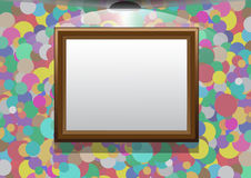 Frame hangs on a colourful wall. The frame hangs on a colourful wall, illumination by a lamp, a place for the text Royalty Free Stock Images