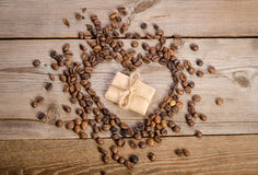 Frame- heart from coffee beans and small parcel inside it Stock Photos