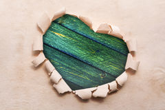 Frame Heart paper border shape dest old wooden. Heart ripped out in the paper and in the middle of desk Stock Photos