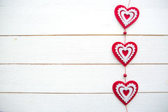 Frame of hearts hanging on white painted wooden background Stock Photography