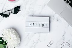 Frame Hello on a marble table with a flower and laptop royalty free stock images
